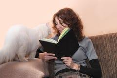 Libro di lettura sorridente del gatto e della donna Fotografia Stock