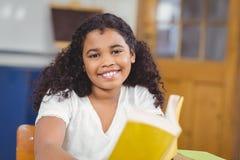 Libro di lettura sorridente dell'allievo in un'aula Immagine Stock Libera da Diritti