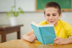 Libro di lettura sorridente dell'allievo in un'aula Immagini Stock