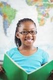 Libro di lettura sorridente dell'allievo in un'aula Fotografia Stock