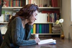 Libro di lettura sorridente della donna sulla tavola di legno Immagine Stock