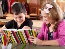 Libro di lettura sorridente della ragazza e del ragazzo al banco Fotografia Stock Libera da Diritti