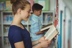 Libro di lettura sorridente della scolara in biblioteca Fotografia Stock