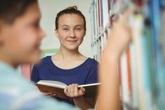 Libro di lettura sorridente della scolara in biblioteca alla scuola Immagine Stock Libera da Diritti