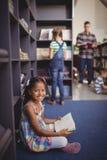 Libro di lettura sorridente della scolara del ritratto in biblioteca Immagini Stock