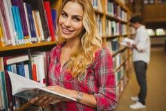 Libro di lettura sorridente della studentessa Fotografia Stock