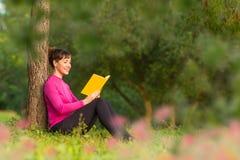 Libro di lettura spagnolo della donna nel parco Fotografia Stock
