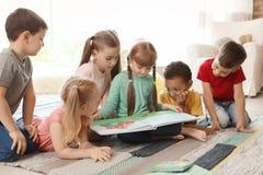 Libro di lettura sveglio dei piccoli bambini insieme all'interno fotografia stock libera da diritti