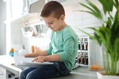 Libro di lettura sveglio del ragazzino in cucina fotografia stock