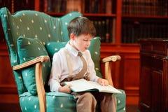 Libro di lettura sveglio del ragazzino sulla poltrona Immagine Stock Libera da Diritti