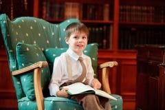 Libro di lettura sveglio del ragazzino sulla poltrona Fotografia Stock
