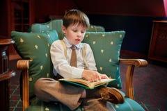 Libro di lettura sveglio del ragazzino sulla poltrona Fotografia Stock Libera da Diritti