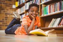 Libro di lettura sveglio del ragazzo in biblioteca Immagine Stock Libera da Diritti