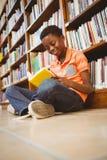 Libro di lettura sveglio del ragazzo in biblioteca Fotografie Stock Libere da Diritti