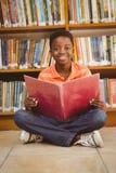Libro di lettura sveglio del ragazzo in biblioteca Fotografia Stock