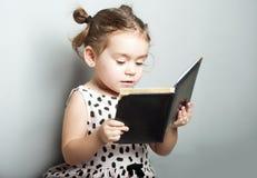 Libro di lettura sveglio della bambina su fondo grigio in vestito rosa Fotografia Stock