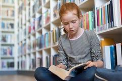 Libro di lettura sveglio della ragazza in biblioteca Fotografia Stock