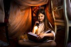 Libro di lettura sveglio della ragazza in casa fatta da sé con la torcia elettrica Fotografia Stock Libera da Diritti