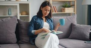 Libro di lettura sveglio dello studente e caffè bevente che si rilassano a casa sul sofà stock footage