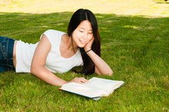 Libro di lettura teenager della ragazza su erba Fotografia Stock Libera da Diritti