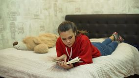Libro di lettura teenager della ragazza sul letto video d archivio