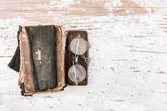 Libro di preghiera antico con gli anni 20 rotondi degli occhiali e caso sulla tavola di legno, sulla vista superiore, sullo spazi Immagine Stock Libera da Diritti