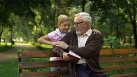 Libro di prima generazione e del nipote di lettura insieme, riposando nelle relazioni di famiglia del parco archivi video