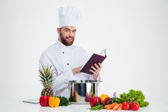 Libro di ricetta della tenuta del cuoco del cuoco unico ed alimento maschii di preparazione Fotografia Stock Libera da Diritti