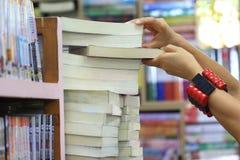Libro di selezionamento femminile della mano dallo scaffale per libri nella stanza delle biblioteche fotografie stock