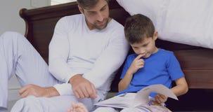 Libro di storia della lettura del figlio e del padre in camera da letto a casa comoda 4k archivi video