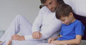 Libro di storia della lettura del figlio e del padre in camera da letto a casa comoda 4k stock footage