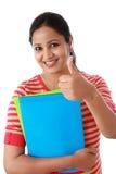 Libro di testo della tenuta della studentessa con il pollice sul gesto Immagine Stock