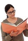 Libro di testo felice della tenuta della studentessa contro bianco Immagine Stock