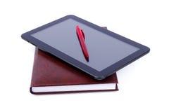 Libro e compressa con la penna Fotografia Stock