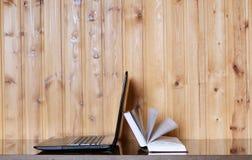 Libro e computer portatile su una tavola di legno Immagini Stock