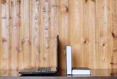 Libro e computer portatile su una tavola di legno Fotografie Stock