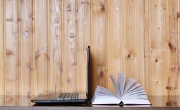 Libro e computer portatile su una tavola di legno Immagine Stock