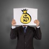 Libro e dollaro di manifestazione dell'uomo d'affari Immagine Stock