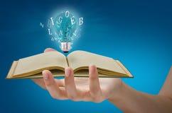 Libro e lampadina a disposizione Immagini Stock