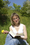 Libro e mela della donna Fotografia Stock