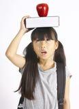 Libro e mela svegli della tenuta della ragazza sulla testa Immagini Stock