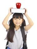 Libro e mela svegli della tenuta della ragazza sulla testa Fotografia Stock Libera da Diritti