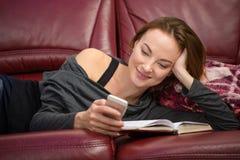 Libro e per mezzo di lettura grazioso sorridente della donna del telefono cellulare Immagini Stock