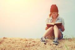Libro e seduta di lettura della ragazza sulla spiaggia con alba Immagini Stock Libere da Diritti