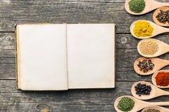 Libro e spezie in bianco di ricetta in cucchiai di legno immagine stock