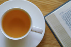 Libro e tazza aperti con tè Fotografia Stock