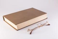 Libro e vetri su un fondo bianco Fotografie Stock Libere da Diritti