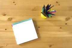 Libro e vetro di schizzo del taccuino con le matite e le penne su una tavola di legno Vista da sopra fotografie stock libere da diritti