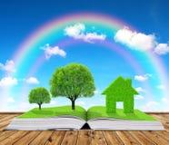 Libro ecologico con gli alberi e casa sulla tavola fotografia stock