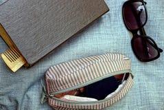 Libro ed occhiali da sole con una borsa aperta sul panno grigio Immagini Stock Libere da Diritti